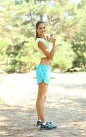 junge schöne Frau, die draußen trainiert foto