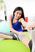 fröhliche junge brünette frau, die zuhause fitnessübungen macht foto