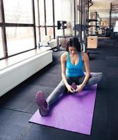 junge Frau, die auf der Yogamatte sitzt und Smartphone verwendet foto
