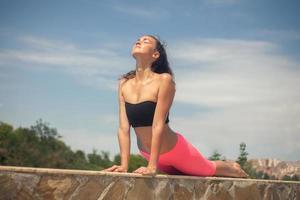 junge schöne Frau, die Yoga draußen am sonnigen Tag tut foto