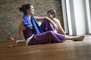 zwei Freunde, die sich nach dem Yoga entspannen foto