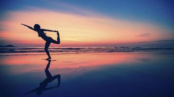 Schattenbild der Fitnessfrau am Strand während des hellen Sonnenuntergangs. foto
