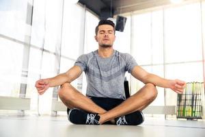 Mann meditiert im Fitnessstudio foto