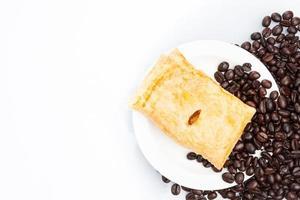 Tasse Kaffee mit Kuchen auf Bohnen. foto