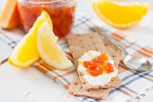 Marmelade im Glas mit Zutaten mit knusprigem Brot foto