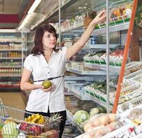 Frau stehend mit einem Einkaufswagen foto