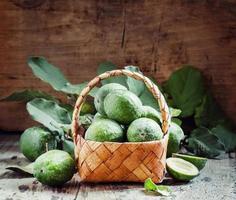 reife grüne Feijoa mit Blättern in einem Weidenkorb foto