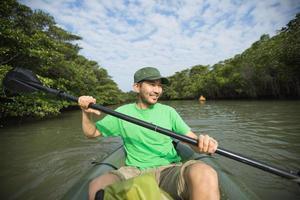Mann, der Flusskajakfahren im Mangrovenwald, Japan genießt foto