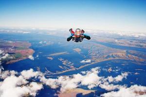 Fallschirmspringer mit Blick auf die Kamera, während er in Richtung Erde fällt foto