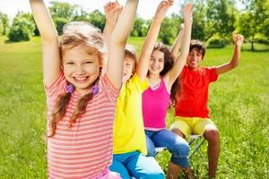 vier Kinder sitzen mit erhobenen Händen in einer Reihe foto