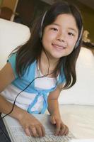 Mädchen, das Musik hört und Laptop verwendet foto