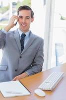 lächelnder Geschäftsmann am Telefon, der Kamera betrachtet foto