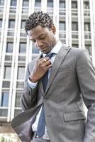 Afroamerikaner-Geschäftsmann, der seine Krawatte anpasst foto