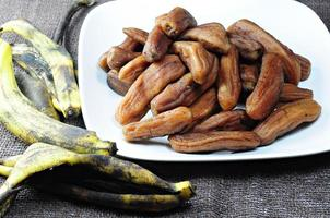 Bananenschale und getrocknete Banane legten einen Teller Weiß.
