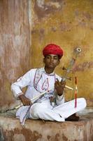 junger indischer Bogen, der Saiteninstrument spielt foto