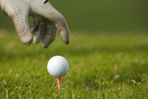 menschliche Hand, die Golfball auf Abschlag, Nahaufnahme positioniert foto