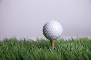 Golfball auf Tee im Gras foto