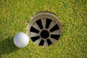 Nahaufnahme des Golfballs in der Nähe des Lochs foto
