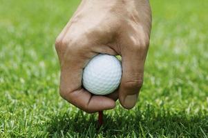 Golfspieler, der Ball auf Abschlag legt, Nahaufnahme foto