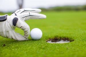 Golfspieler Mann schiebt Golfball in das Loch foto