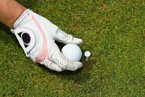 behandschuhte Hand, die Golfball auf Abschlag legt foto