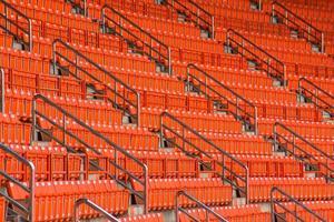 rote Sitze auf der Tribüne der Stadionstufen foto