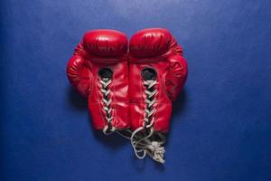 Paar rote Boxhandschuhe auf blauem Lederhintergrund foto