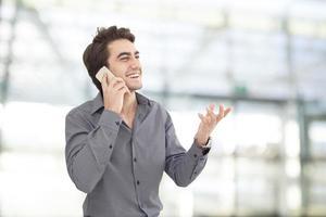 junger Geschäftsmann, der Handy im Büro spricht foto