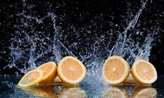 geschnittene Zitrone im Wasser auf schwarzem Hintergrund