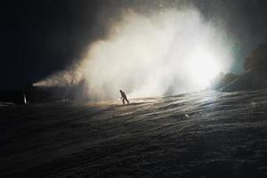 Skifahrer in der Nähe einer Schneekanone, die Pulverschnee macht. Alpenresort. foto