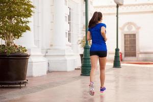 junge Frau läuft in der Stadt foto