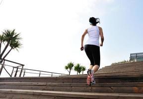 asiatische Frau des gesunden Lebensstils, die an Holztreppen hochläuft foto