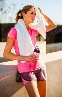 Fitnessfrau wischt Gesicht mit Handtuch weg foto