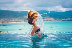junge Frau taucht aus dem Wasser auf foto