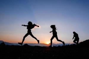 glückliche Freunde, die auf Bergen laufen foto