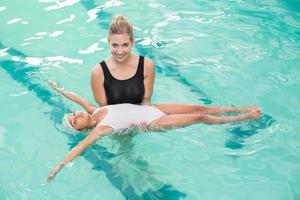 süßes kleines Mädchen, das lernt, mit Trainer zu schwimmen foto