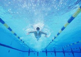 Unterwasseraufnahme des männlichen Schwimmers, der im Pool schwimmt foto