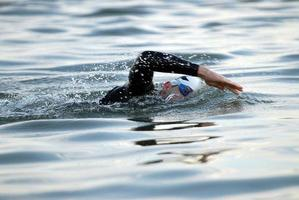Triathletenschwimmer im offenen Wasser foto