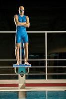 junger hübscher Sportmann, der durch das Schwimmbad aufwirft foto