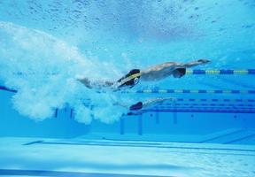Unterwasseraufnahme von drei männlichen Athleten, die im Schwimmbad rennen foto