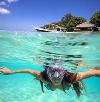 eine junge Frau unter Wasser schwimmen foto
