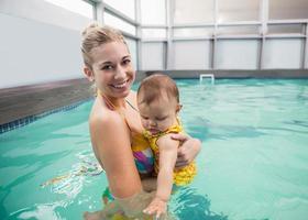 hübsche Mutter und Baby am Pool foto