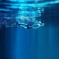 Mann schnorchelt auf blauem Hintergrund, Unterwasseransicht foto