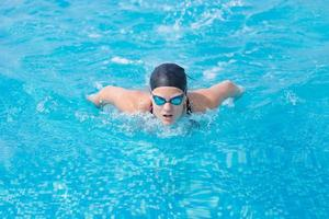 junges Mädchen, das Schmetterlingsschlagart schwimmt foto