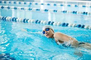 junges Mädchen in der Schutzbrille, die Frontkriechschlagart schwimmt foto