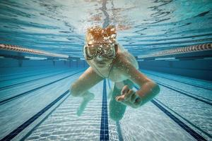 Junge schwimmt unter Wasser foto