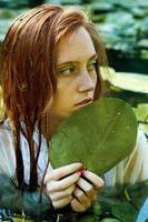 zarte junge Frau, die im Teich schwimmt foto