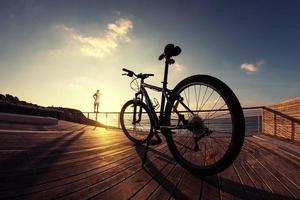 Schattenbild des Sportlers und des Mountainbikes bei Sonnenuntergang foto