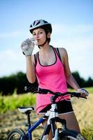gesunde fröhliche junge Frau, die Mountainbike im Freien in der Landschaft reitet foto