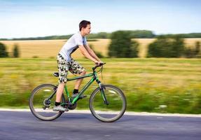 Teenager, der Fahrrad fährt foto